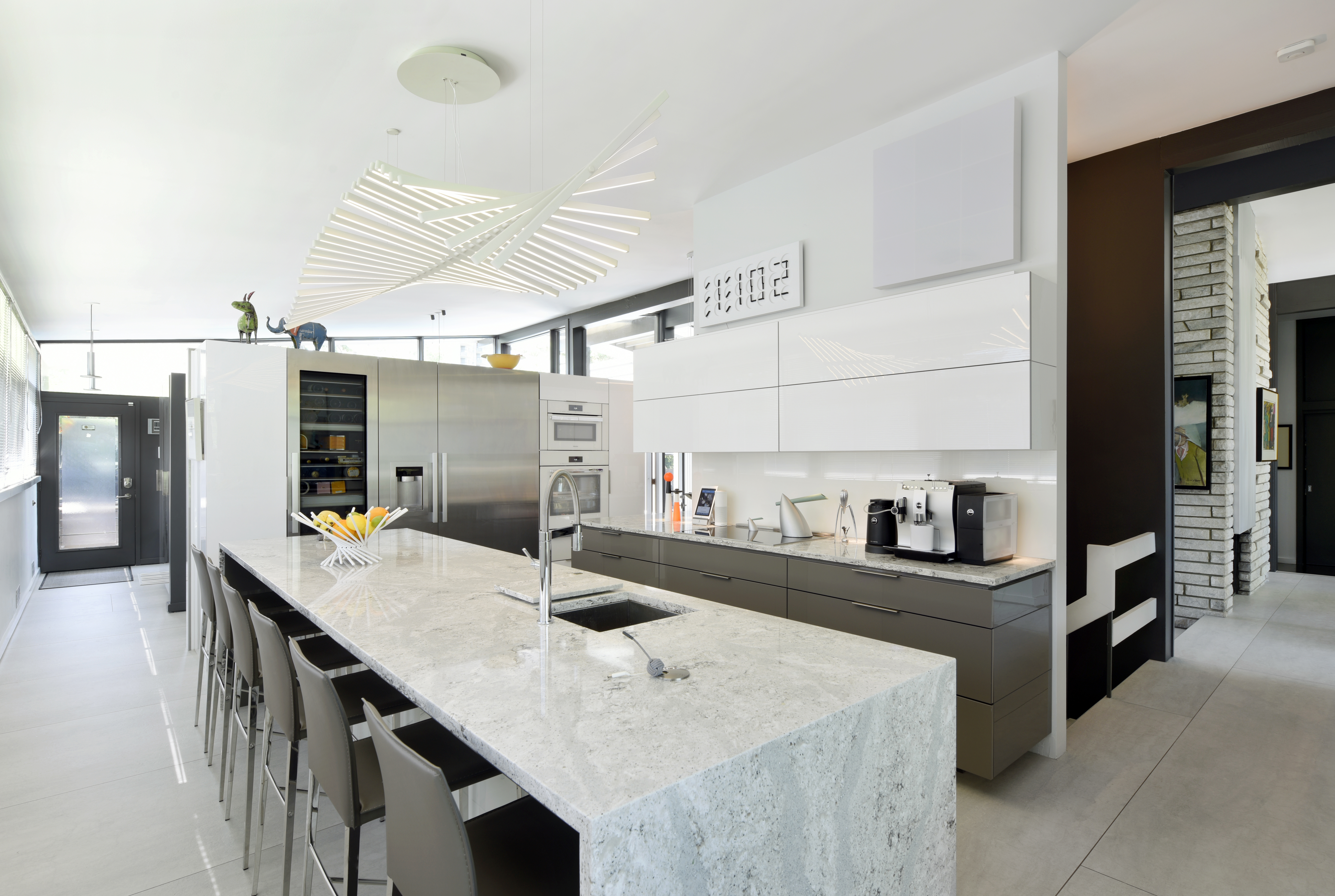 A row of modern bar stools in an upscale kitchen.