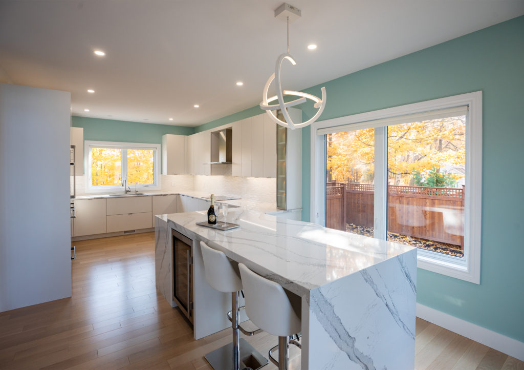 A kitchen design with a coastal theme and a waterfall island countertop.