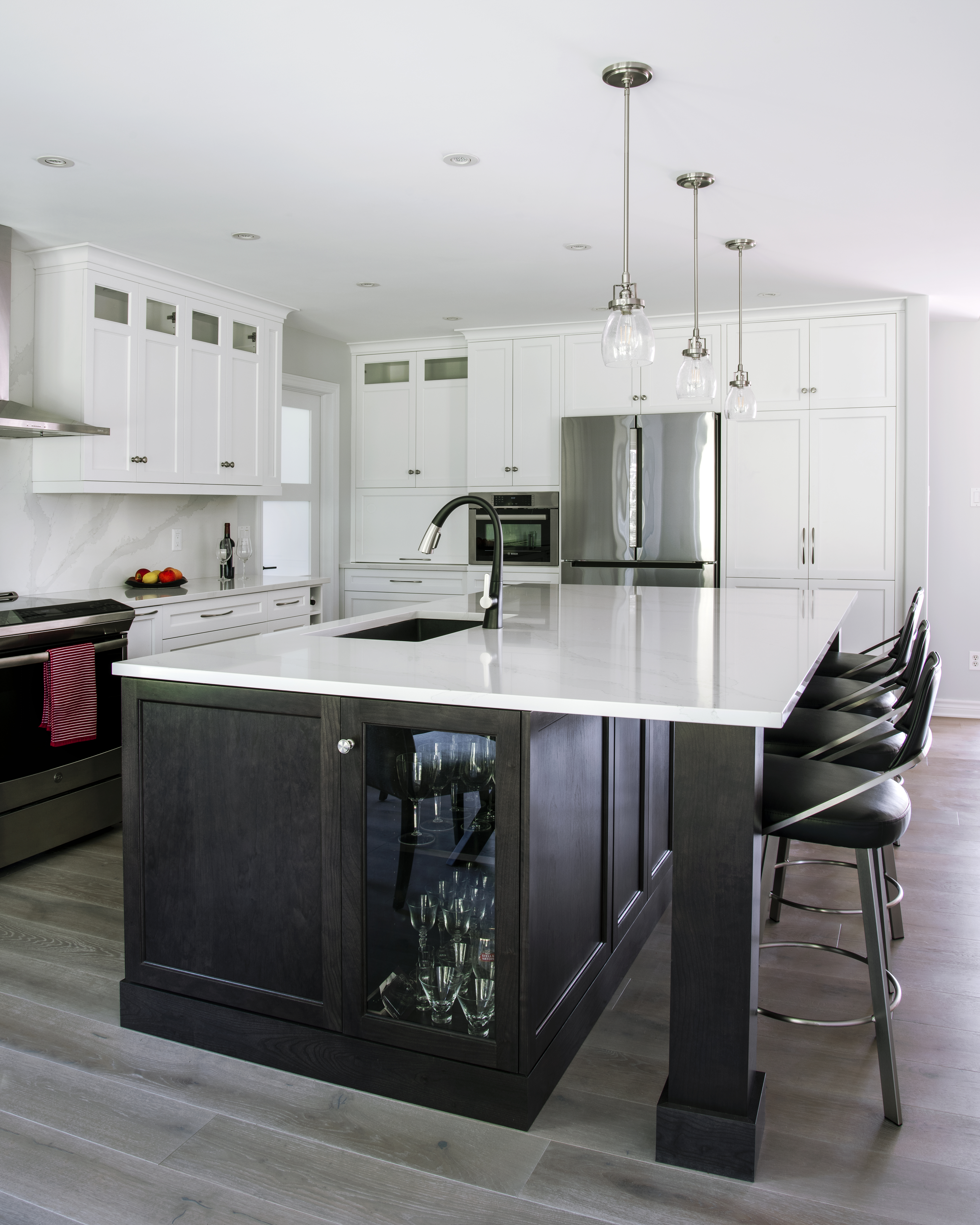 A white kitchen with a dark cherry island in the centre.