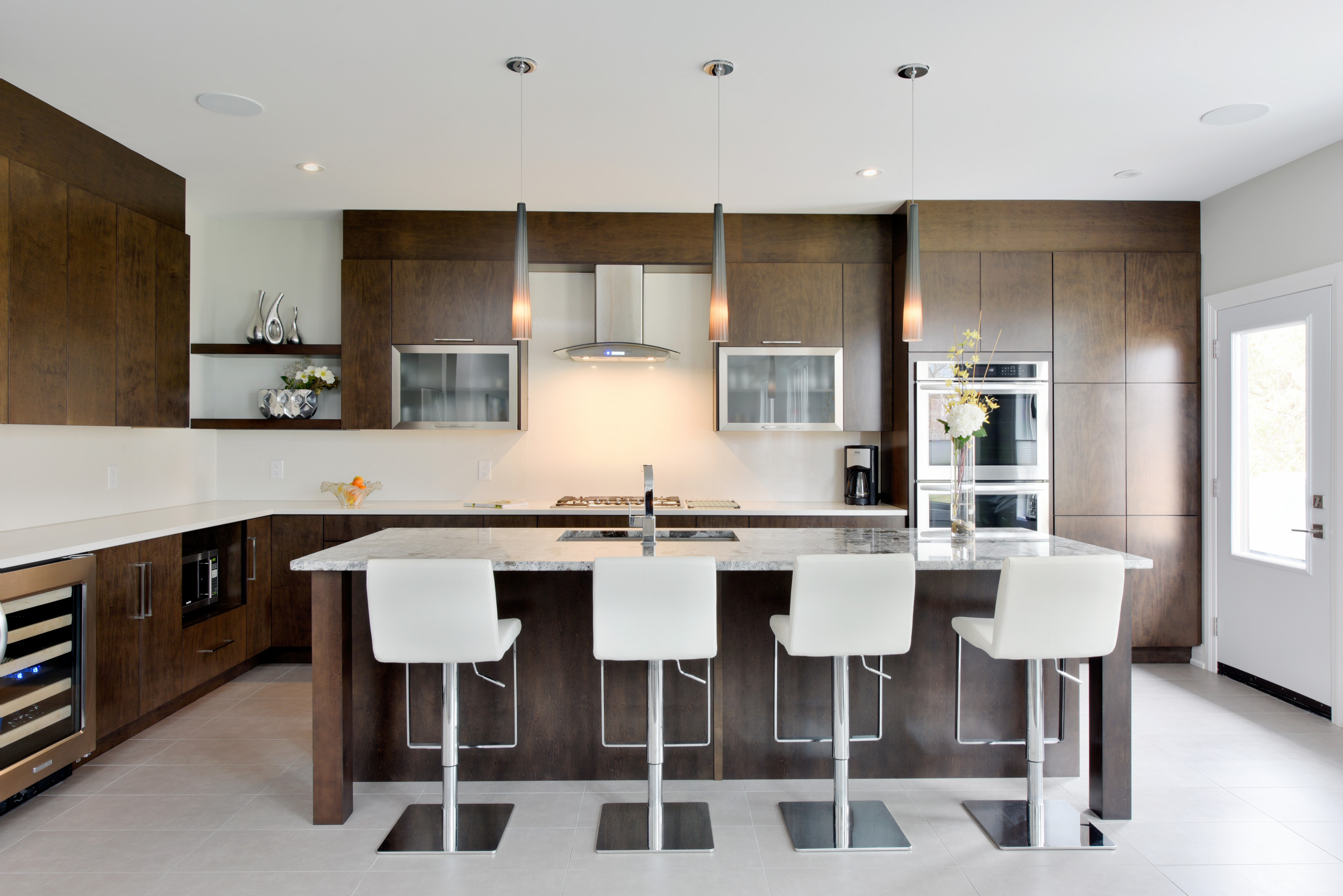 Glass cabinets with stainless steel frames on either side of the range