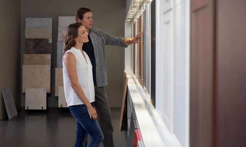 Homeowners exploring kitchen design options in a showroom.