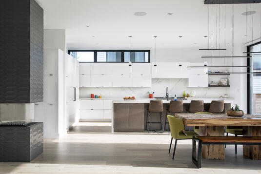 A spacious, white-themed kitchen area with natural light.