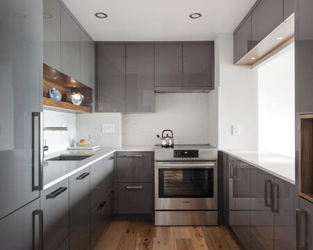 A high-gloss custom cabinetry system with a gray colour scheme.