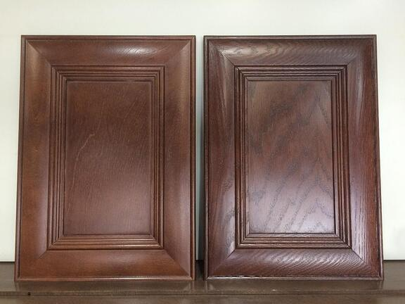 A stained oak and birch cabinet door side by side.