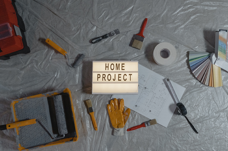 """A collection of painting tools and a sign that says """"Home Project""""."""
