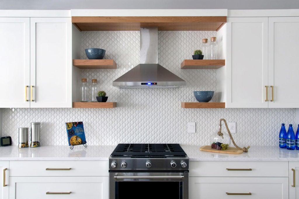 A custom kitchen with a tiled backsplash, floating shelves, and range hood.