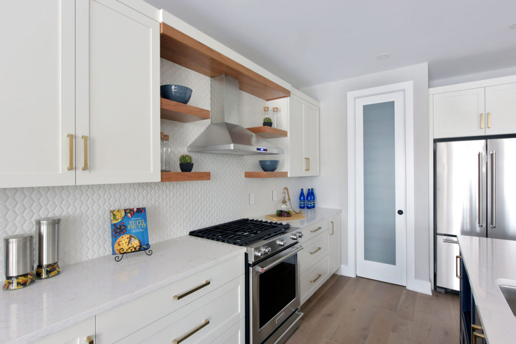 A gas stove and hood range in a custom kitchen design