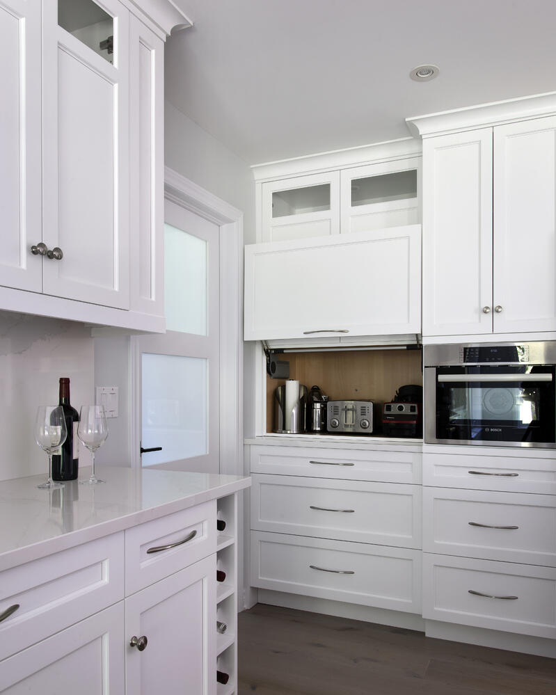 A white kitchen with a mix of both knobs and pulls for hardware.