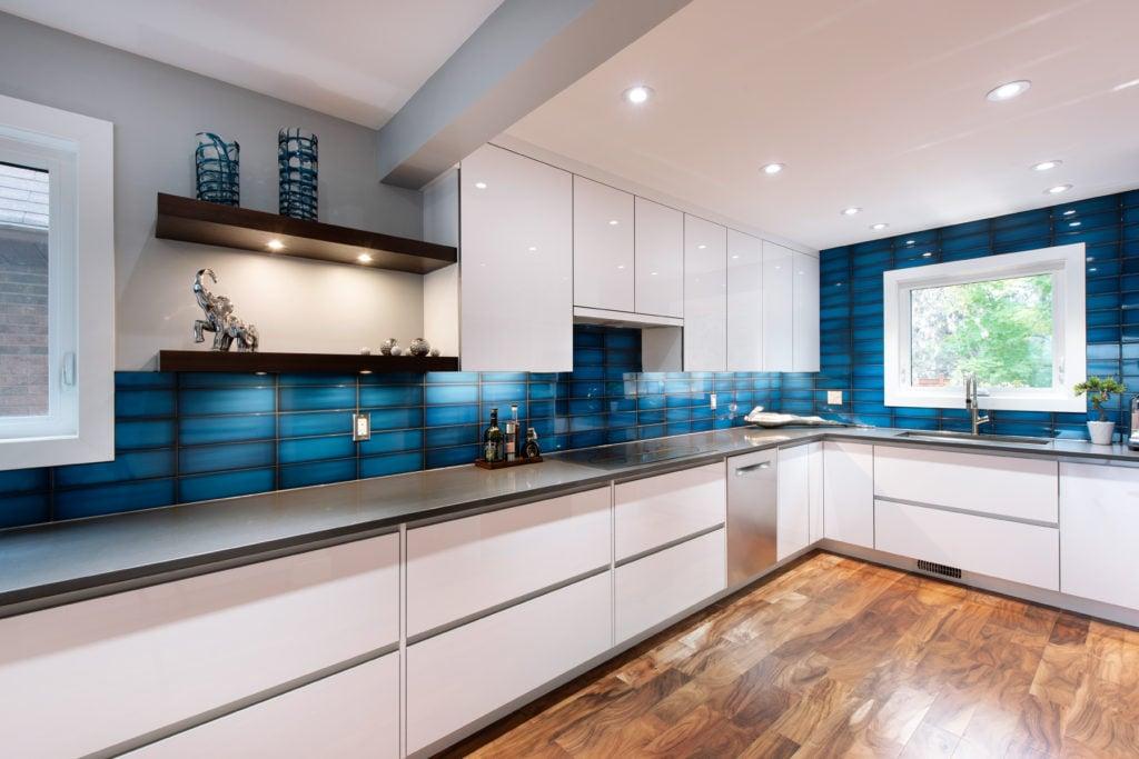 A modern Deslaurier kitchen with a bright blue backsplash.