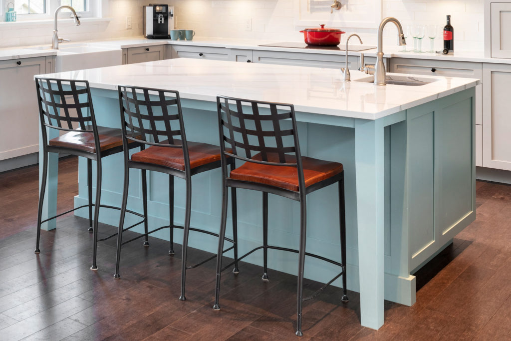 A kitchen island with a deep counter depth and tucked in bar stools.