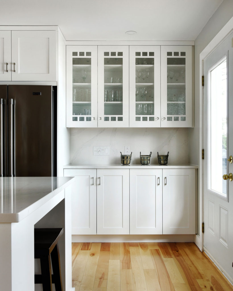 Glass cabinetry next to an open window.