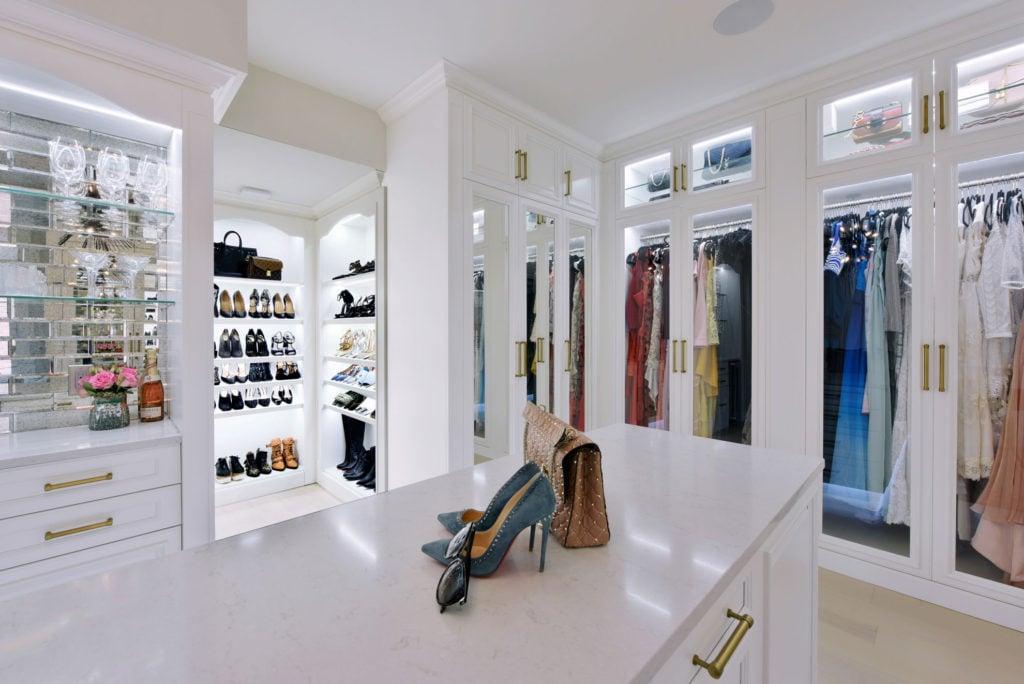 A high-end custom closet featuring built-in shoe racks