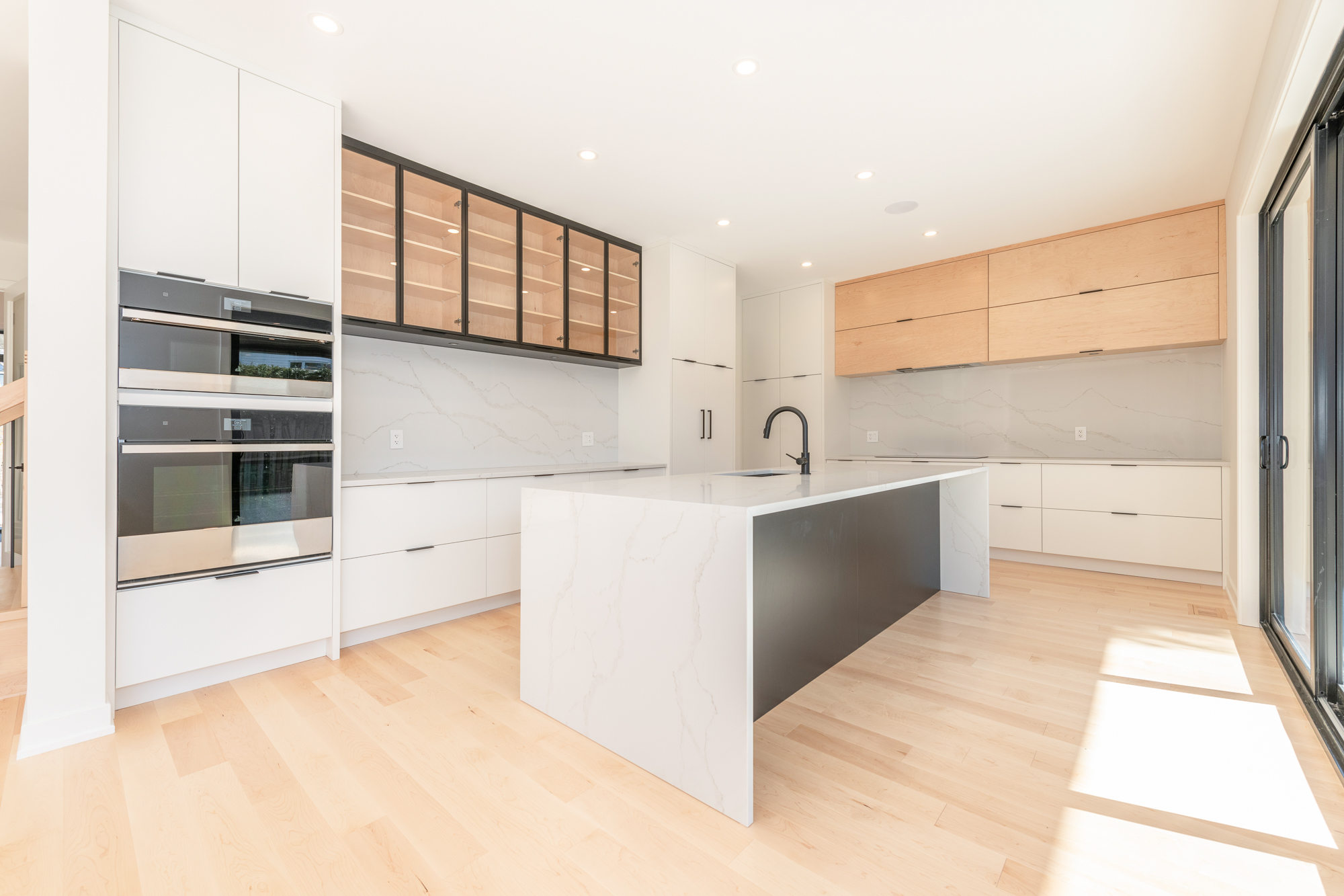 A brand-new kitchen by Deslaurier with empty shelving.