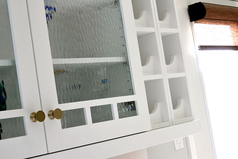 A kitchen with architectural mullion glass upper cabinets