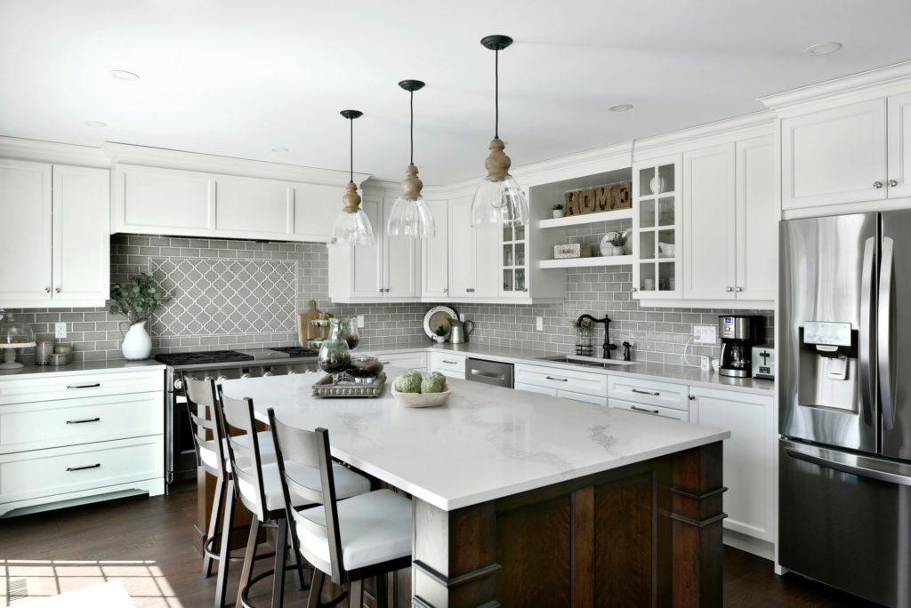 A custom kitchen with white cabinets and a grey tiled backsplash.