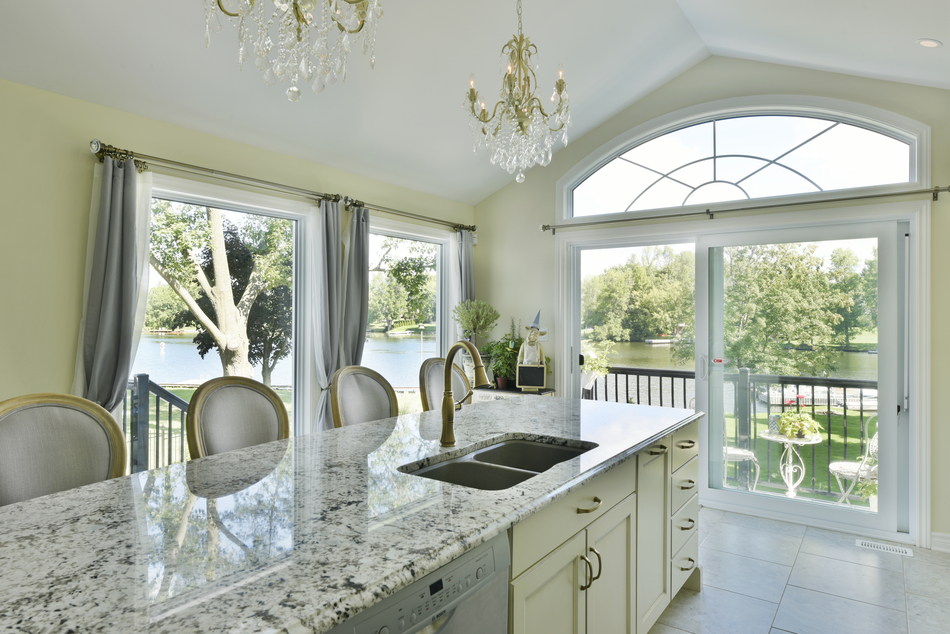 A speckled granite countertop on a kitchen island in a traditional kitchen design.