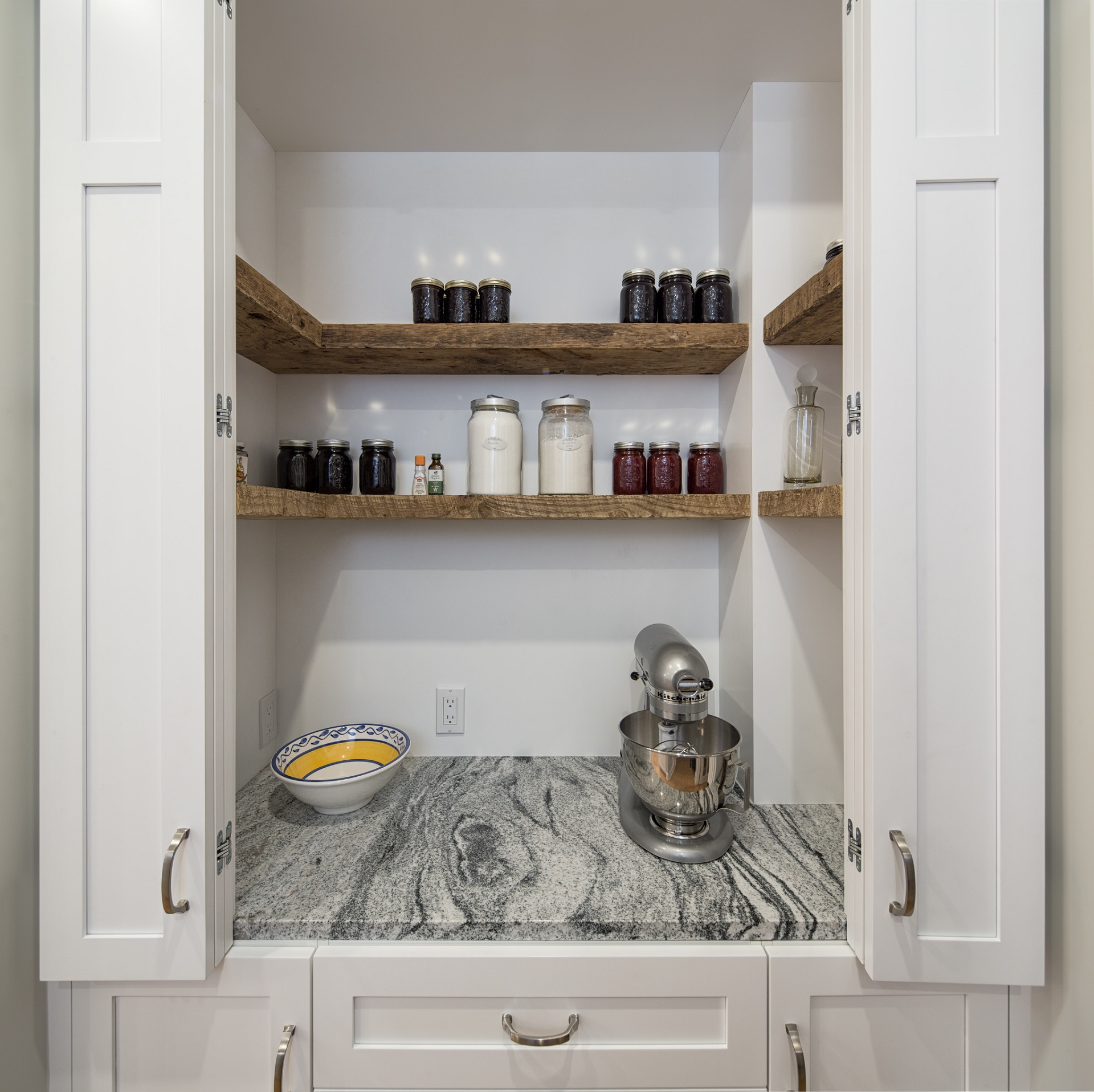 A pantry with wooden floating shelves.