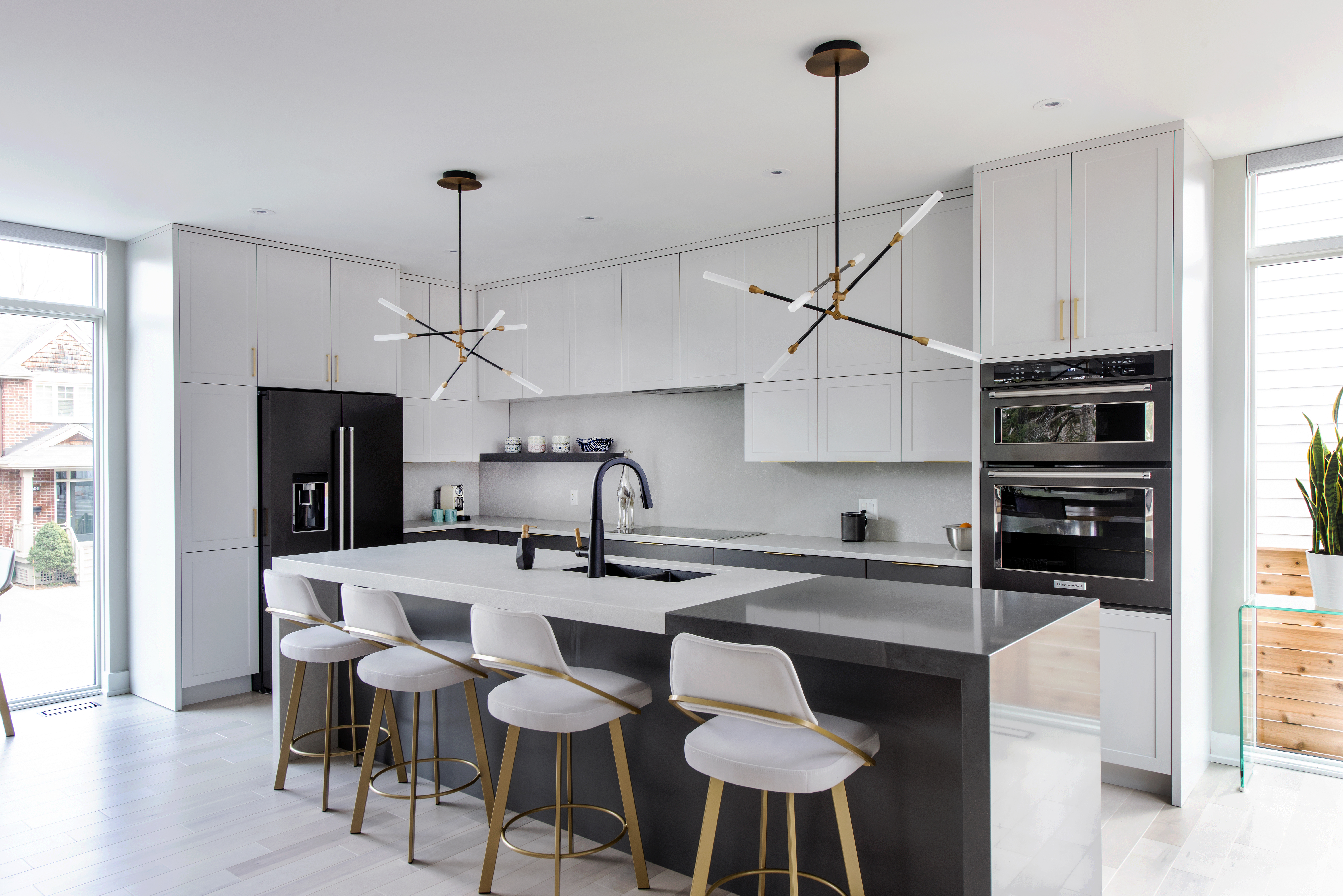 A two-toned quartz waterfall countertop in a Deslaurier kitchen.