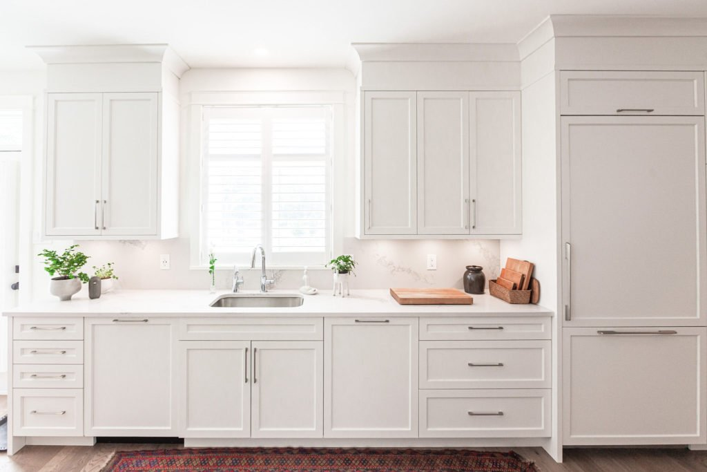 A kitchen that extends cabinets to ceiling height with bulkhead trim and crown moulding.
